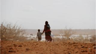 Woman and little boy walking on a dry land.