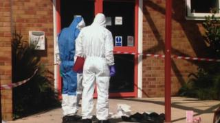 Forensic officers look down at the buildings entrance