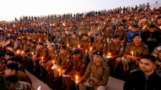 Central Reserve Police Force and Rapid Action Force soldiers and their family members hold candles as they pay tribute to personnel during a candlelight vigil in Bhopal