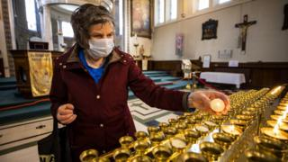 A woman wearing a face mask lights candles at a church in Northern Ireland