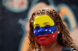 Mujer que tiene la bandera de Venezuela pintada en el rostro