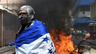 A student of the National Autonomous University of Honduras (UNAH) wrapped in a Honduran national flag is seen next to a fire that blocks a road during a protest against the approval of education and healthcare bills in the Honduran Congress in Tegucigalpa on April 29, 2019