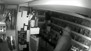 CCTV image shows thief examining bottles of vodka