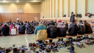 Refugees pray in the gym of the Sweden's largest temporary camp for refugees at the former psychiatric hospital Restad Gard in February 2016 in Vanersborg, Sweden