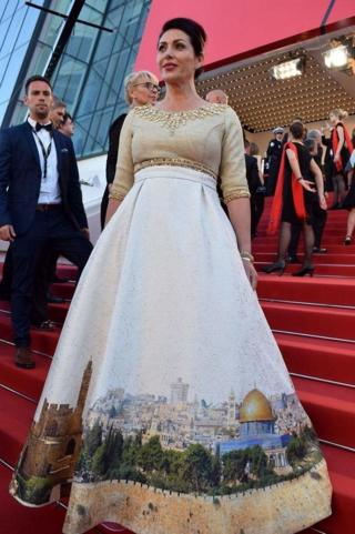 """Israeli Culture Minister Miri Regev wearing a dress featuring the old city of Jerusalem arrives on May 17, 2017 for the screening of the film """"Ismael""""s Ghosts"""" during the opening ceremony of the 70th edition of the Cannes Film Festival in Cannes, southern France"""
