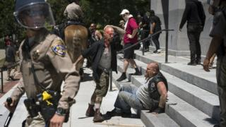 Wounded men sitting on steps of California State Capitol after members of right-wing extremist groups clashed with counter-protesters in Sacramento, Sunday, June 26, 2016