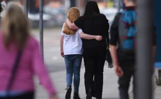 فتاة وامرأة يمشيان بعيدا عن الكاميرا