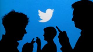 пользователи с телефонами на фоне логотипа Twitter