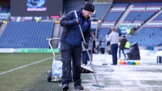 Ground staff clear the Murrayfield pitch after snowfall in Edinburgh