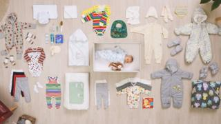 The contents of a Finnish maternity box, plus baby
