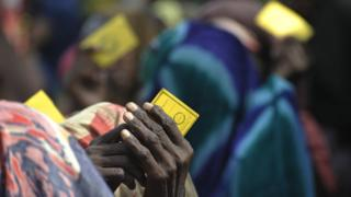 Residents of a camp for Internally Displaced Persons (IDP) hold their ratio card as they queue to receive aid in Mogadishu on August 13, 2011