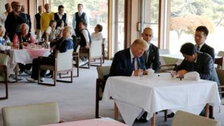 特朗普(前左)与安倍晋三(前右)在埼玉县霞关乡村俱乐部餐厅内于鸭舌帽上签名(5/11/2017)
