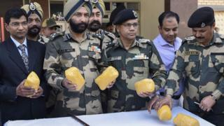 File photo: Indian border security force officers show off packets of confiscated heroin found near the India-Pakistan border , 18 February 2017