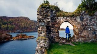 Female tourist at the ruins of Strome Castle on the shores of Loch Carron