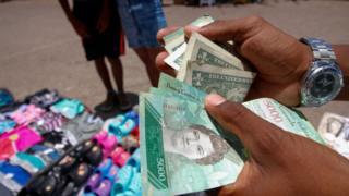 Hombre con bolívares y dólares en la mano.