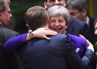 Theresa May greets European Council president Donald Tusk at the EU summit in Brussels