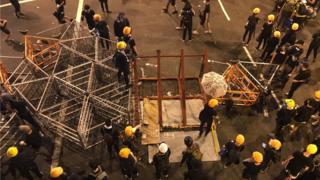 示威者集結做路障,從遠處運來更多的鐵欄。