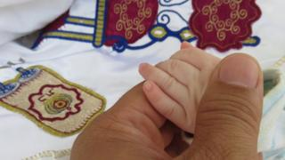 A father holds a baby's hand before circumcision