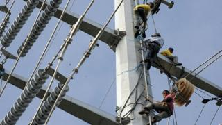 Linemen install cables on the Transco power transmission line in Santa Rosa town south of Manila on January 15, 2009