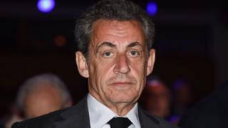 Nicolas Sarkozy, dressed in a dark suit and tie at night, looks directly into the camera in this close-up 2018 photo