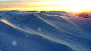 A sunset over snowy hills