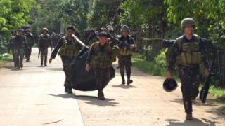 Troops carry bodies after a military operation against the Islamist militant group Abu Sayyaf in Sulu province, southern Philippines