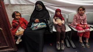 Women and children sitting in a temporary medical centre