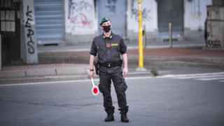 Italian Guardia di Finanza officers wearing protective face masks man a checkpoint between Corvetto and Rogoredo in Milan
