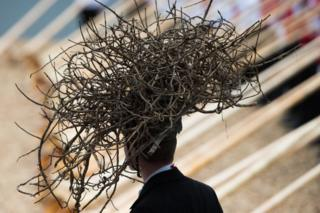 A man wearing a headdress made of twigs during the opening ceremony of the Gotthard rail tunnel - 1 June 2016