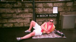 A man wearing shorts, sunglasses and a towel around his shoulders lies on a blanket on the floor in front of a street sign