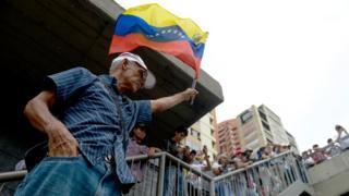 Hombre mayor sostiene bandera de Venezuela.
