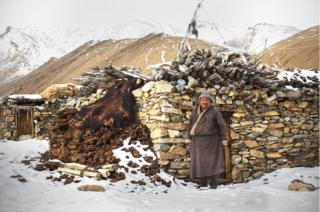 A herder stands in front of his stone house