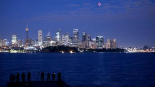 The moon is seen turning red over the Sydney skyline during a total lunar eclipse on July 28, 2018 in Sydney, Australia.