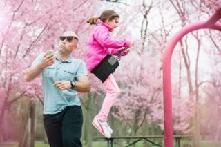 Мужчину с телефоном сбивают качели дочери