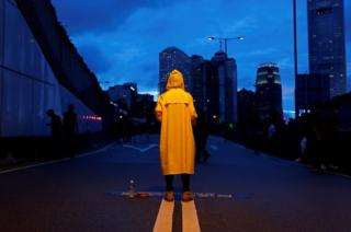 A protester wears a yellow raincoat to pay tribute to a man who died while protesting
