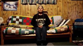 Jean Whitehorse sentada em um sofá em casa. Mulher é uma das nativas americanas que nos anos 70 foi esterelizada contra a vontade