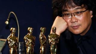 O diretor Bong Joon Ho ao lado de estatuetas do Oscar