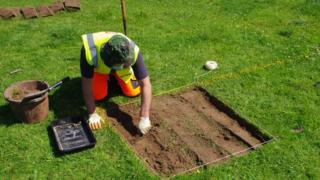 A man digging a small square in turf