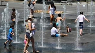 A group of people pictured trying to stay cool in a fountain