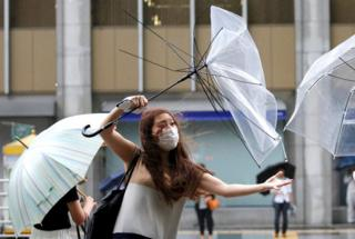 A woman using an umbrella struggles against heavy rain and wind