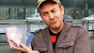 Alexander Lapshin holding his passports for Russia, Israel and Ukraine.