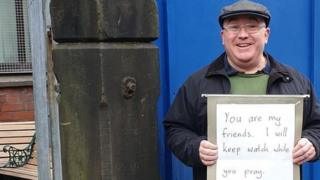 "Andrew Graystone holding placard saying: ""You are my friends. I will keep watch while you pray."""