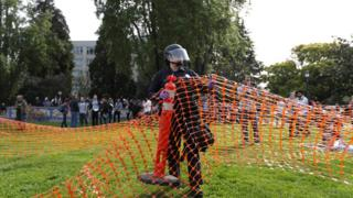 一名警员架起塑胶围栏,分隔开特朗普的支持者和反对者。