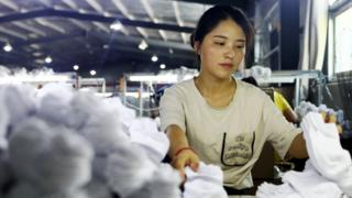 A woman works on socks that will be exported to the US at a factory in Huaibei in China's eastern Anhui province on August 7, 2018