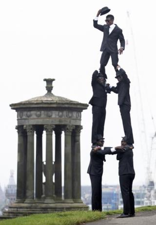 Five acrobats stand in a triangle shape on top of Calton Hill in Edinburgh.