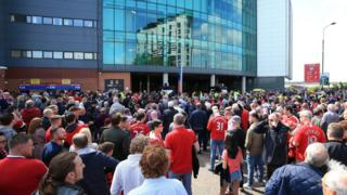 Fans wait outside Old Trafford
