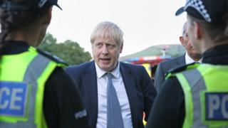 Prime Minister Boris Johnson meeting police during a visit to Whaley Bridge Football Club in Derbyshire, after the Toddbrook Reservoir near the village of Whaley Bridge was damaged in heavy rainfall