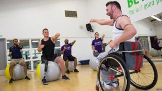 Kris teaching a gym class. Amputee model Jack Eyers is there and apart from Kris they are all doing a punching movement while sitting on gym balls