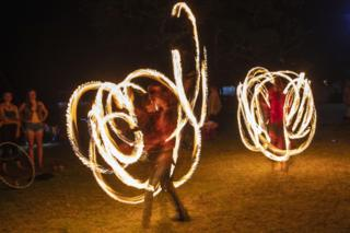 Fire poi performers entertain the crowds as the festival waits for midnight to celebrate the New Year during the annual AfricaGrow Festival of Friends, in the Wilderness, with closest town being Plettenberg Bay, South Africa, 31 December 2019