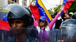 A supporter of self-proclaimed acting president Juan Guaidó, demonstrates behind a line of police officers in Caracas on March 9, 2019